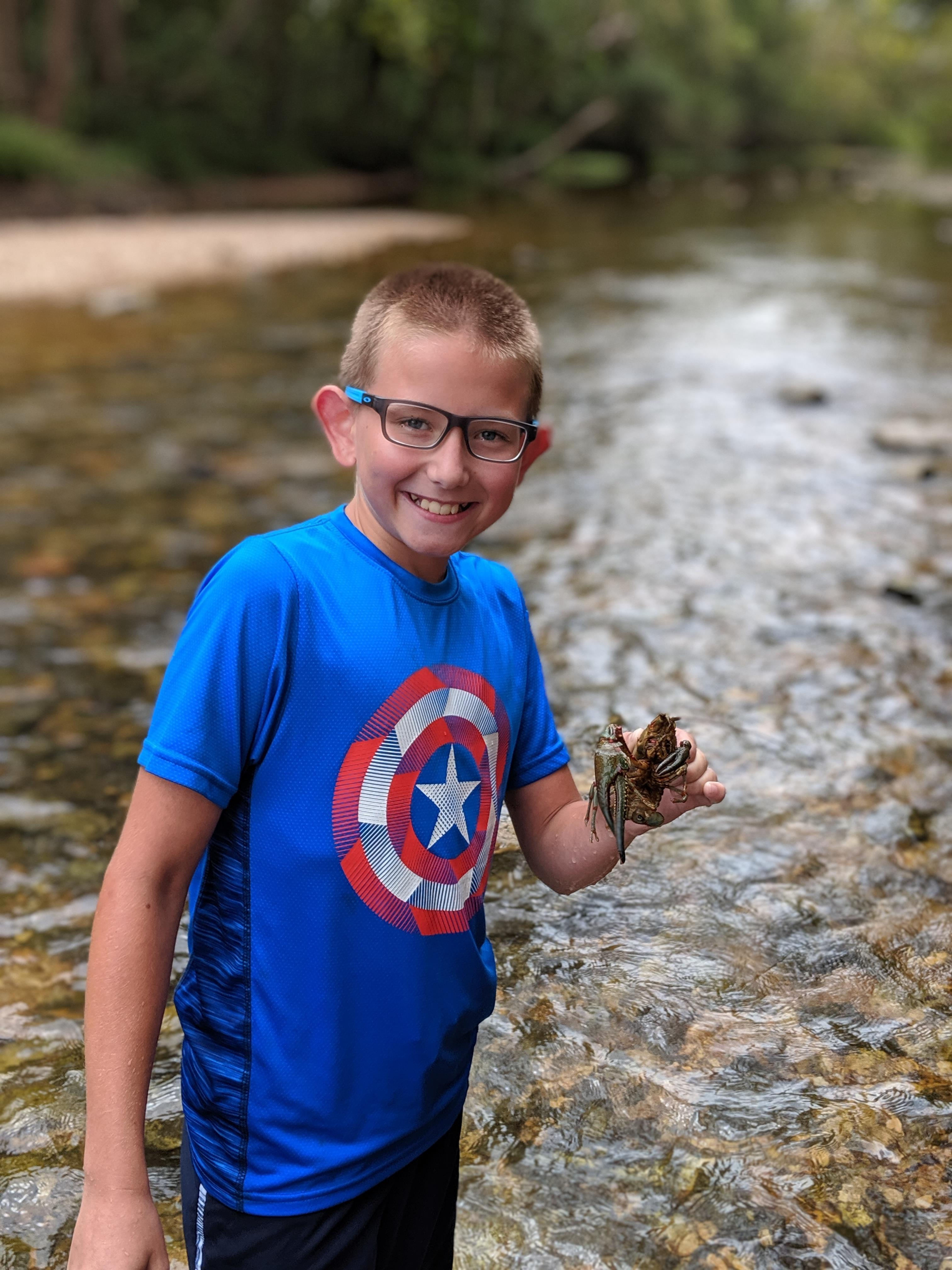 Young boy in stream with macroinvertebrate