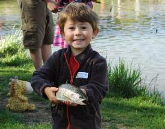 A young boy holding a fish he just caught at a National Fishing and Boating event. Photo credit: USFWS