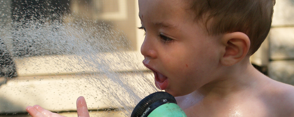 Young boy drinking from hose