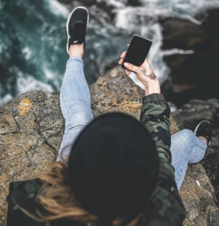 Young woman sitting on cliff with phone